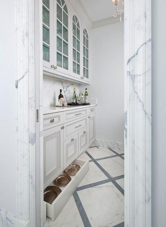 A white pocket door is surrounded by a marble trim and opens to a white and gray butler's pantry boasting white and gray cabinets fitted with nickel knobs and a statuary marble countertop accented with a marble slab backsplash located under glass front upper cabinets while a hidden toe kick drawer provides extra storage.