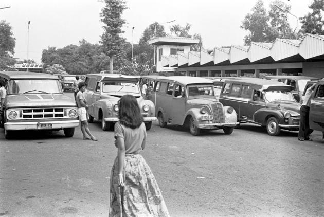 1980-Perempuan lewat di depan deretan oplet di terminal Cililitan, Jakarta. Dulu, pabrik karoseri untuk memodifikasi oplet terletak di daerah Meester Cornelis, atau kini disebut Jatinegara.