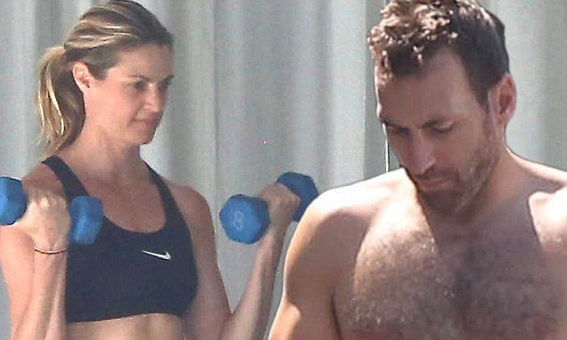 Erin Andrews works out while husband Jarret Stoll cleans the garage