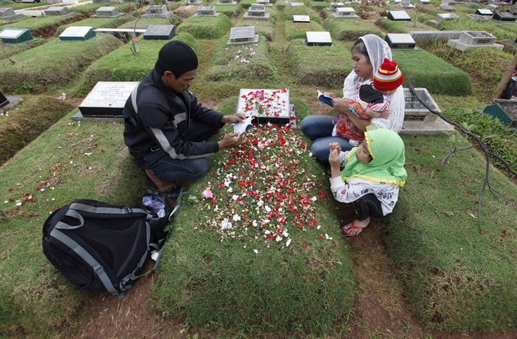 Observing Ramadan | A family reads verses from the Koran at a relative's grave in a cemetery, a day before the Islamic holy month of Ramadan, in Jakarta, on July 9, 2013. Traditionally Indonesian Muslims will visit the graves of their relatives before and towards the end of the the holy month. | The Atlantic /Reuters/Enny Nuraheni