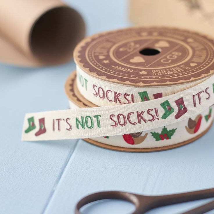 It's Not Socks! Christmas Ribbon. A fun little Christmas ribbon in natural white, green and red emblazoned with festive stockings and the words 'It's not socks!'