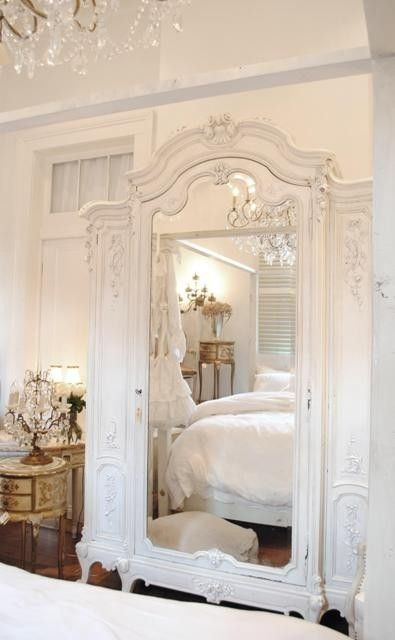 Gazing through the mirror in a soothing all white feminine bedroom. So inviting!