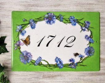 Questa targa per numero civico è dipinta a mano su una piastra ovale di porcellana (13x18 cm. nelle foto) decorata con una composizione di fiori di gelsomino ed edera. Una targa come questa darà un tocco personale alla vostra casa!  Personalizza la tua targa: puoi scrivere il tuo indirizzo, il numero civico, un nome o una citazione letteraria...verrà dipinto a mano sulla targa secondo i tuoi desideri.  Questa piastra può essere anche utilizzata come targa per indirizzo da esterno o come…