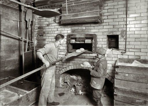 De bakker doet het brood in de oven.