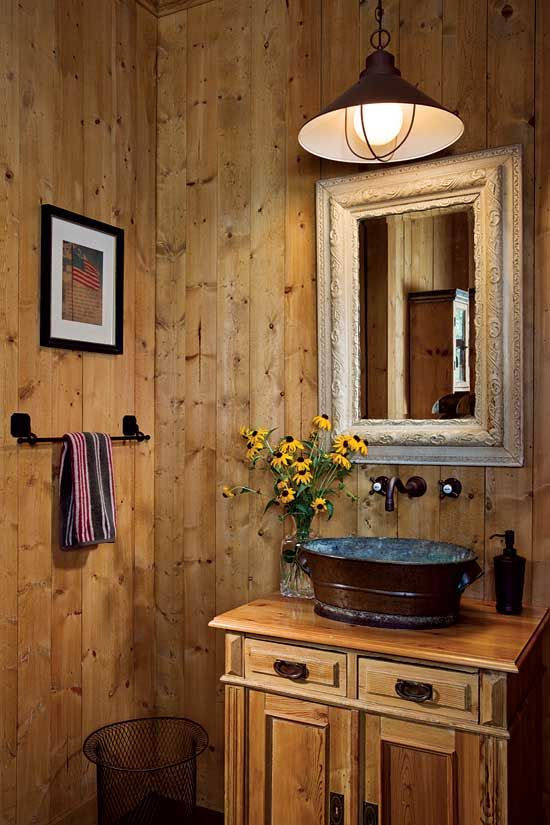 Wood walls and western details, such as the copper basin sink and outdoor pendant light, add rustic charm.