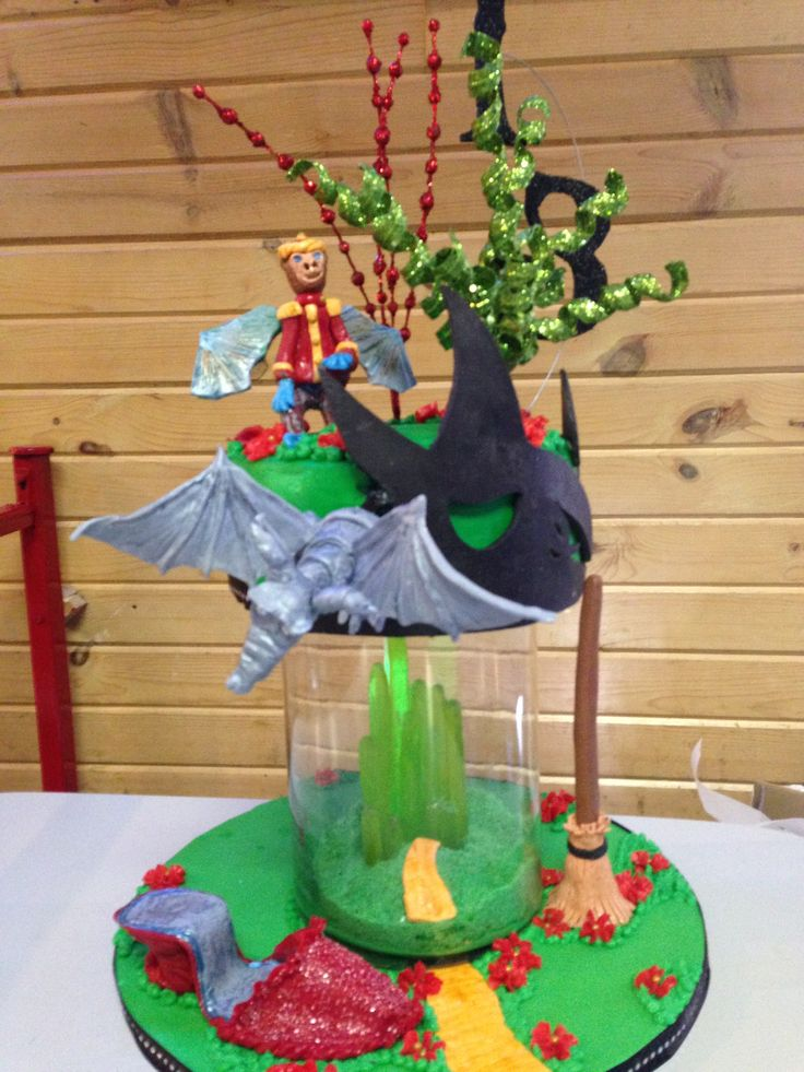 Wicked! Cake with modeling chocolate flying monkey, ruby slipper, the Time Dragon, and Elphaba.  The Emerald city was formed using green apple Jolly Ranchers and backlit with a glow stick.