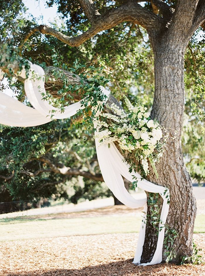 Try this to create unique wedding arbor: drape the low-hanging branch of a beautiful, tall tree with white chiffon and lush flowers. #weddingarbor #weddingideas #weddingceremonyideas