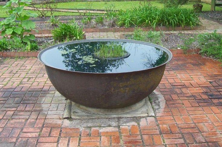 fuente redonda de metal con plantas acuáticas