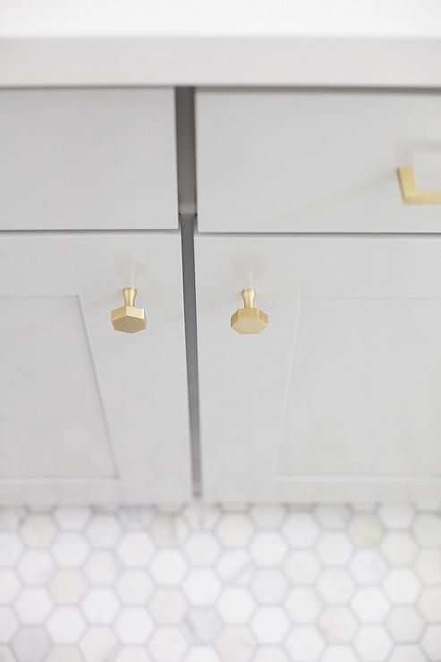 Gold and gray bathroom is filled with a gray shaker vanity adorned with brushed brass hexagon knobs topped with white quartz.