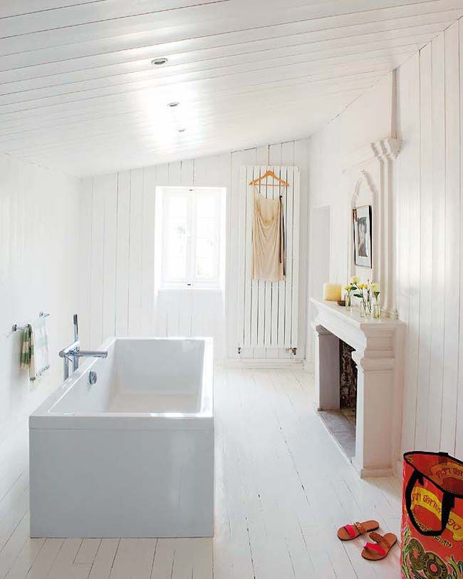 White Wooden Bathroom with Sloped Ceiling containing: Rectangular Bathtub with Floor Mount Tub Faucet also Shelf Top Fireplace