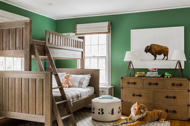 Fabulous boy's bedroom features hunter green walls framing Restoration Hardware Kenwood Twin Over-Full Bunk Bed in Driftwood. The Animal Print Shop's American Buffalo Print sits over a vintage trunk dresser with 7 drawers adorned with leather handles topped with tripod table lamps alongside Land of Nod Numbers Pouf and stuffed tiger atop white and beige trellis rug.