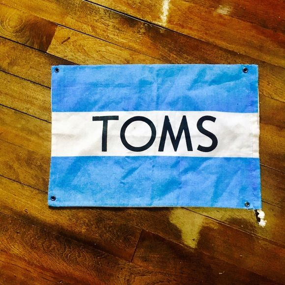 "TOMS One-For-One Flag Supporter of TOMS? Want a different decoration for your room? This is the flag for you! And that's not all, it's a bag too! Size is 14"" by 9.5"" TOMS Bags"