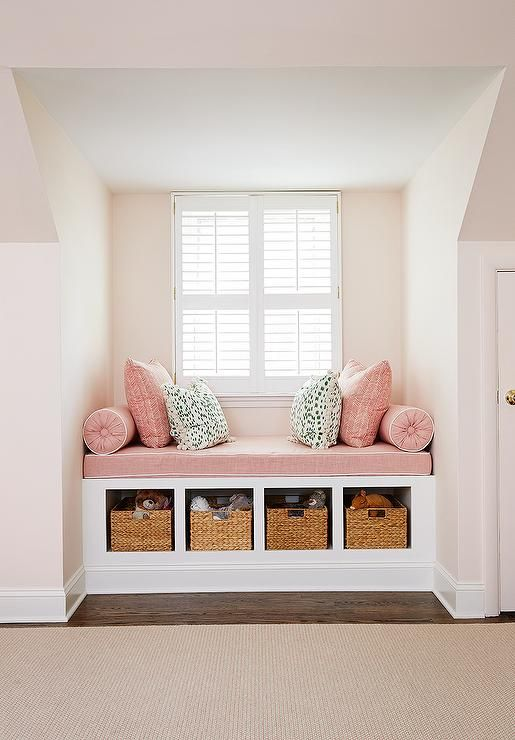 Pink girl's room features a nook filled with a built-in window seat fitted  with