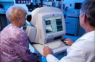 An eye care professional uses optical coherence tomography (OCT) to obtain a detailed cross-sectional image of the back of the eye.   Please credit National Eye Institute, National Institutes of Health.