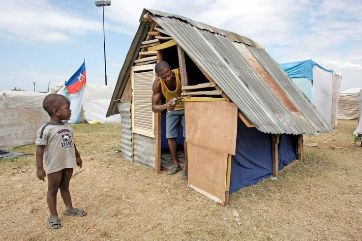 January 26th, 2010: A child from the tent cit watches as Idner Lund builds a house from scraps of wood and metals he found in the destroyed neighborhoods surrounding the tent city called, Mais Gate near Port-au-Prince airport.