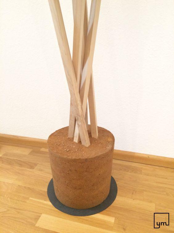 Eichenholzlatten in Lehmsockel gestampft: Holzlatten unten mit einem Draht grob in Form gebracht und in einen Eimer gestellt. Lehm schichtweise in den Eimer stampfen. Auch die Zwischenräume der Latten müssen gut mit Lehm umstampft werden, damit es stabil wird.Nach Trocknung mit Klopfen auf den Eimer lässt sich die Garderobe herauslösen...und fertig! Richtige Lehmmischung verhindert Rissbildung und gibt dem Sockel eine schöne farbliche Schichtung. Viel Spaß beim Ausprobieren!