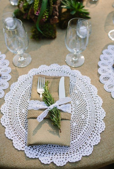 This beige and white table setting plays with texture, from a burlap napkin holder and tablecloth to a crochet doily and lace napkin ring. A sprig of sage adds a splash of color.