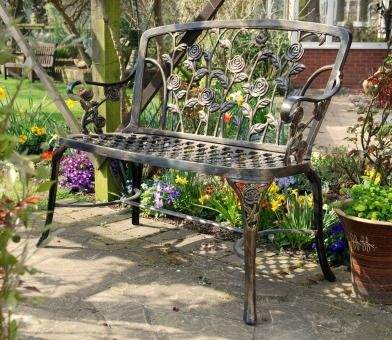 The delightfully rustic Rose Metal Garden Bench looks superb in dappled sunshine