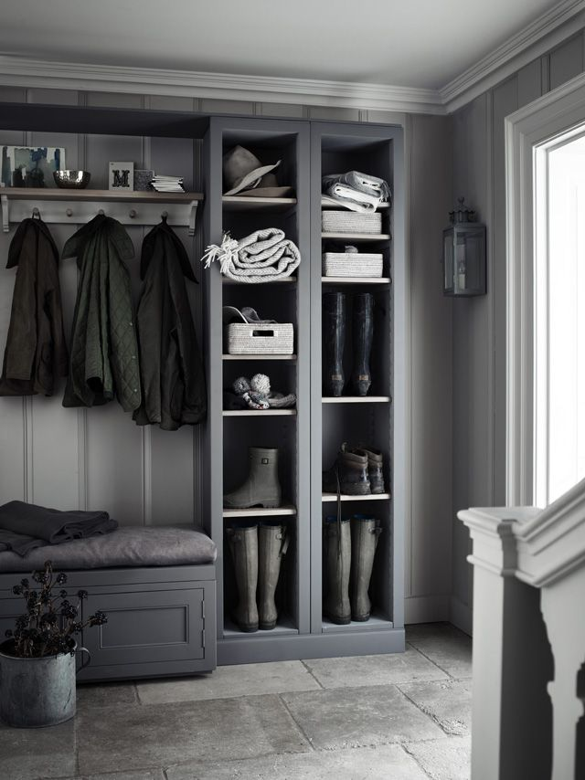 Grey boot room with open shelves, pegs for coats and a bench for perching on.