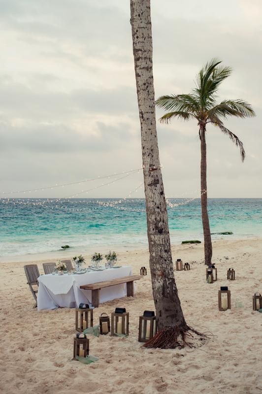 Candlelit reception on the beach under palm trees and string lights | Photography by Amanda Temple Photography