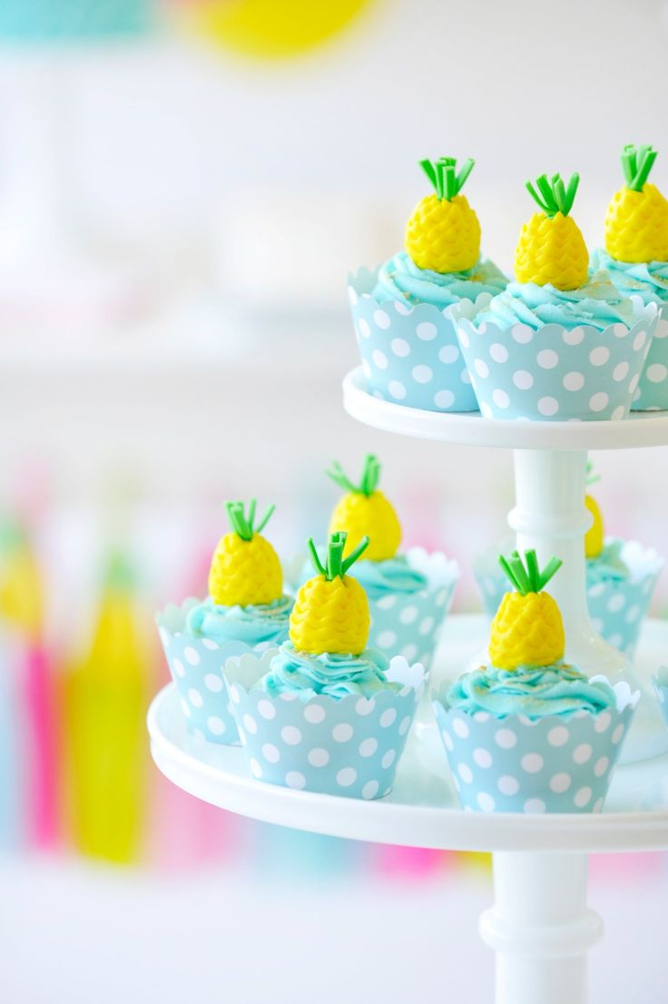 Summer themed aqua birthday cupcakes. Edible yellow and green pineapple cupcake toppers. Aqua and white polka dot cupcake cases. Flamingo Party styling by Happy Wish Company. Photography by Tammy Hughes Photography. Stationery by Minted artist, Laura Hankins.