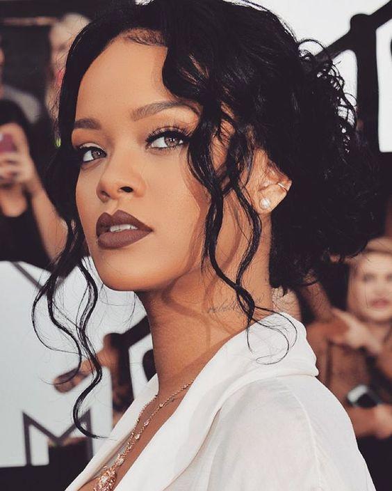 Rihanna arrasando com batom marrom e cílios postiços + cabelo preso baixinho com fios soltos
