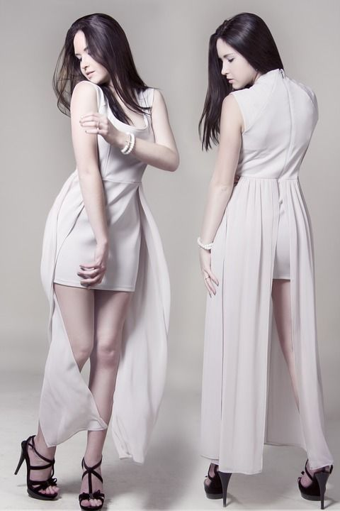 White sleeveless dress with short skirt and long sheer back worn with black strappy high heels.