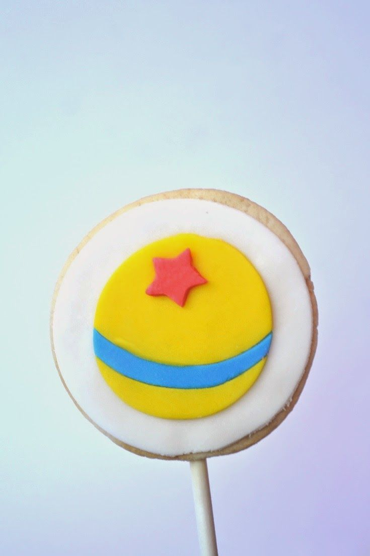 """A less well known """"character"""" of Toy Story: the Luxo Ball (a.k.a. Pixar Ball). It has made appearances in other Pixar movies. It is a yellow ball with a blue stripe and red star. This cookie was made with fondant. (birthday, Andy)"""