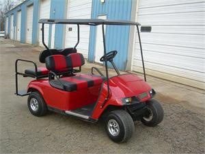 2008 EZ-GO PDS RED / BLACK ELECTRIC GOLF CART    Red EZ-Go golf cart with red and black stripped seats and black sun top. 36 volt electric golf cart with additional rear seats, lights and charger for the golf cart battery.