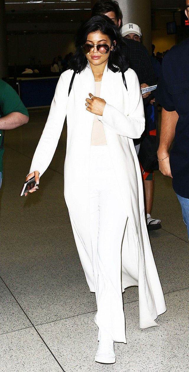 Kylie Jenner looks sleek in a long white jacket, neutral top, cropped pants, high-top sneakers, and mirrored sunglasses