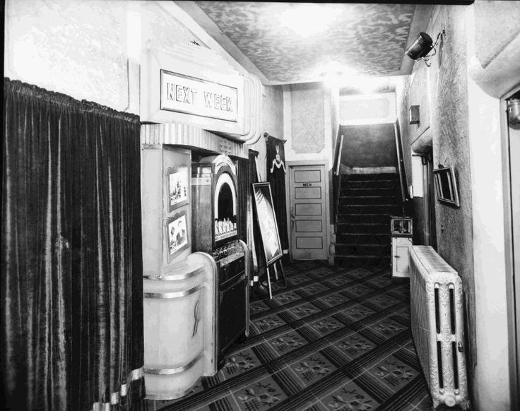 https://flic.kr/p/rftARC | Lyceum Theatre, Interior | Date: c. 1930s Description: This photograph shows a interior hallway at the Lyceum theatre in Port Arthur, ON. Each of the curtained doorways (at left, foreground and background) lead into the theatre seating area. Advertisements for upcoming productions plaster the walls. It's unclear what is being sold in the vending machine in the centre of the photo, but given the time period and the venue, it's a toss up whether it's concession…