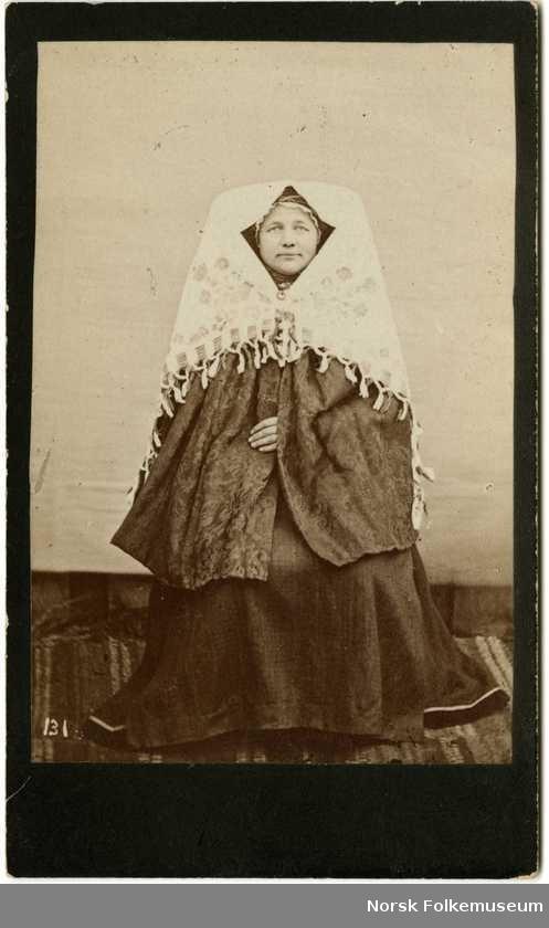 Digitalt Museum - 131. Brudedrakt, fra Grungedal, Vinje, Telemark. Kvinne sitter i fotoatelier med nøytral bakgrunn og mønstret gulvteppe. Visittkortformat. Fra nasjonaldraktserie tatt av fotograf Knud Knudsen (1832-1915), Bergen.