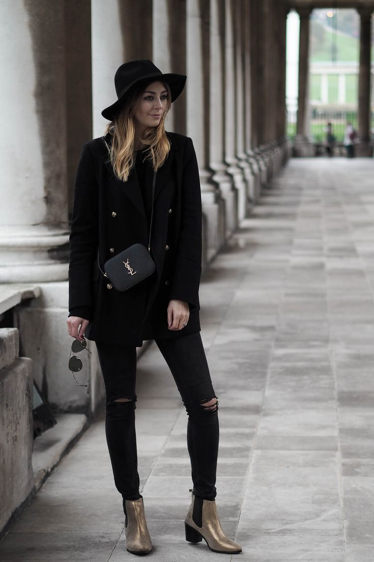 black military coat, skinny jeans, YSL camera bag, gold details, gold ankle boots, fedora hat, all black outfit