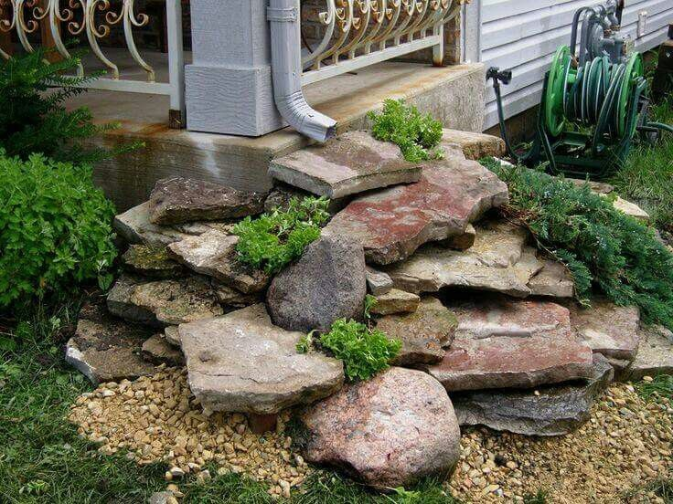 downspout drainage idea to stack flat rocks for a mini waterfall by the deck downspout onto hill