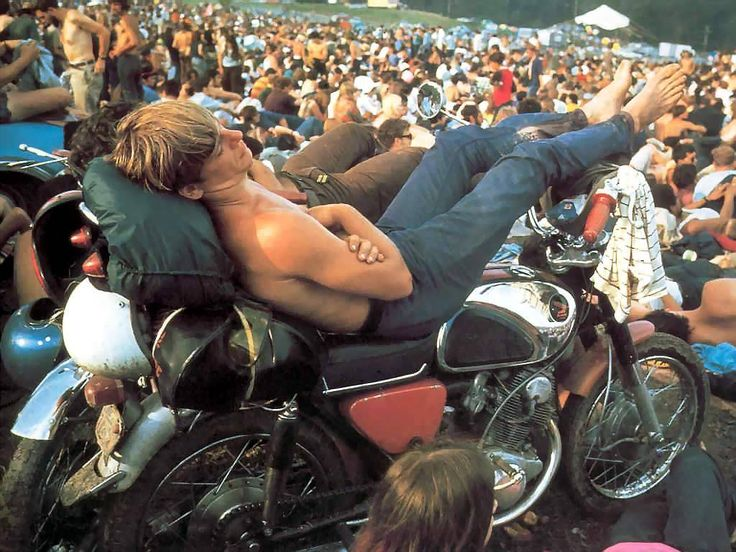 A guy sleeping at his motorbike during Woodstock