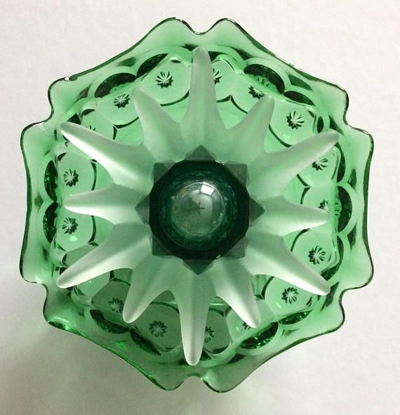 This one of a kind glass creation features a green six sided cut glass dish, frosted sunburst votive holder, emerald green glass votive holder with a large iridescent marble in the center. The glass is adhered with silicon glue that is waterproof and sun/freeze proof. I do