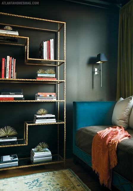 Saturated teal sofa and the shiny brass bookcase