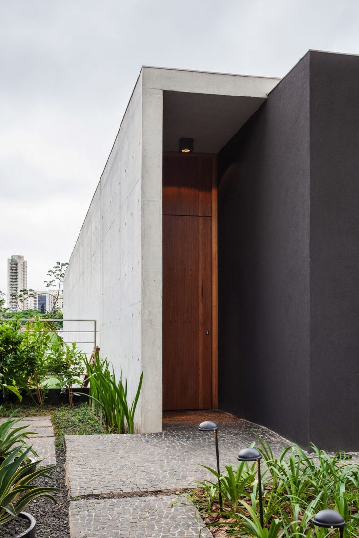 The narrow Mattos House sits on a slope within the hilly city. A series of three platforms step down from the home's entrance to a terrace at the base of the incline.
