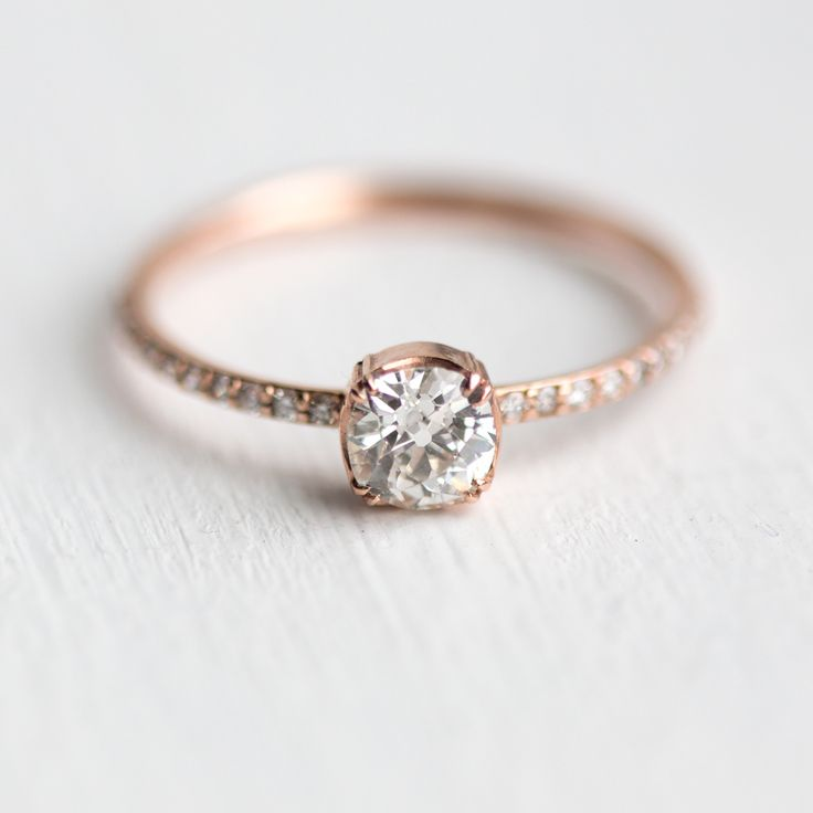 This elegant, antique-inspired engagement ring features a completely unique old European cut diamond focal diamond set in prongs on a slim, dainty band with tiny white diamonds running down the sides.