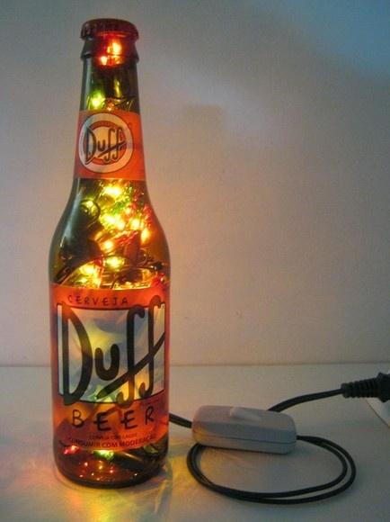 Luminária produzida com garrafa de vidro da marca Duff, cerveja consumida pelo personagem Homer Simpson. É o presente perfeito para colecionadores e admiradores da série Os Simpsons. Além de original, a luminária é um presente que colabora com a preservação ambiental.  Ideal para cabeceiras, estantes e escrivaninhas. Combina também com ambientes comerciais como lojas, bares e restaurantes.  Características: - São 100 microlâmpadas coloridas que permitem uma boa iluminação. - Acompanha…