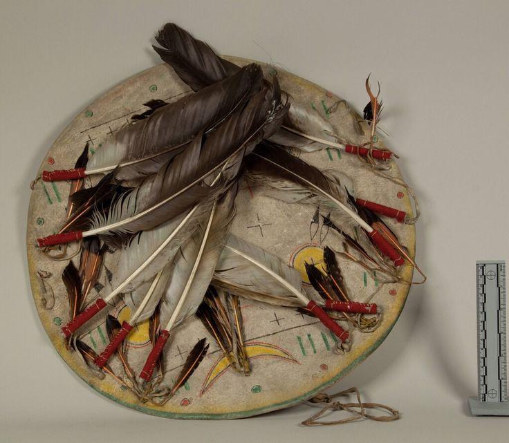 """Щит c покрышкой, Шайены. Вид один. Из """"Oklahoma Historical Society, Temple Houston Collection"""". Дизайн щита включает птиц, геометрические фигуры, полумесяц. Цвета: жёлтый, красный, чёрный, зелёный. Ремни на краях щита, орлиные перья.  Донор Victor J. Evans. Щит был изготовлен White Horse, незадолго до его смерти.  Дата поступления 20 Maрта 1931 года.  NMNH - Anthropology Dept."""