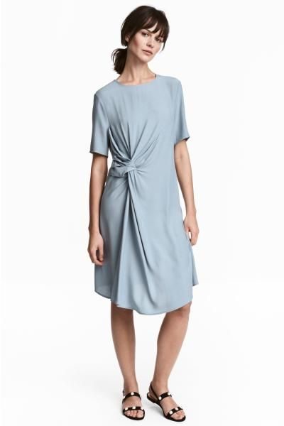 Šaty z krepové tkaniny v délce ke kolenům. Mají krátký rukáv. Vpředu mají uzlový detail a jsou řasené. Průstřih s knoflíkem vzadu u krku. Bez podšívky.