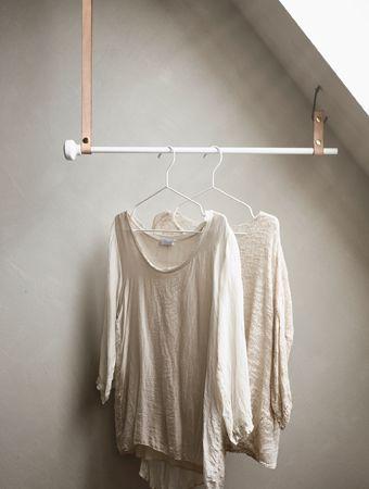 Aan een stang die met leren riempjes aan het schuin aflopend plafond hangt, hangt kleding op kleerhangers