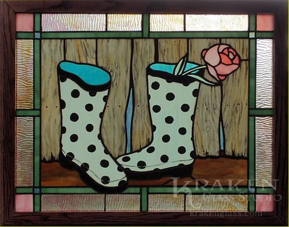 A pink peony swoons over the edge a polka-dot galosh, one of a pair in front of a white-washed barn.The barn wood textureis hand pained with permanent, kiln-fired enamel and glass paints that aredetailed with knots, nail heads, and dry rot. The teal galoshes are also emblazoned with enamel paint details from from head to toe. The scene is bordered with wood-grain textured cathedral glass - just another detail that really makes this piece so special!  www.krakenglass.com