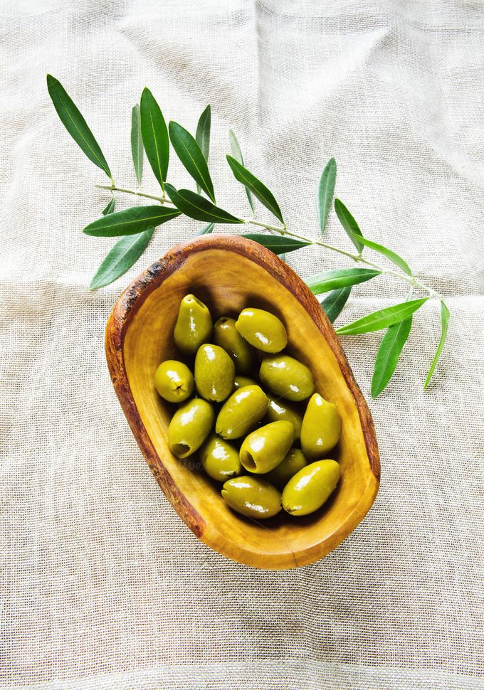 olives in a wooden bowl  by IriGri on @creativemarket