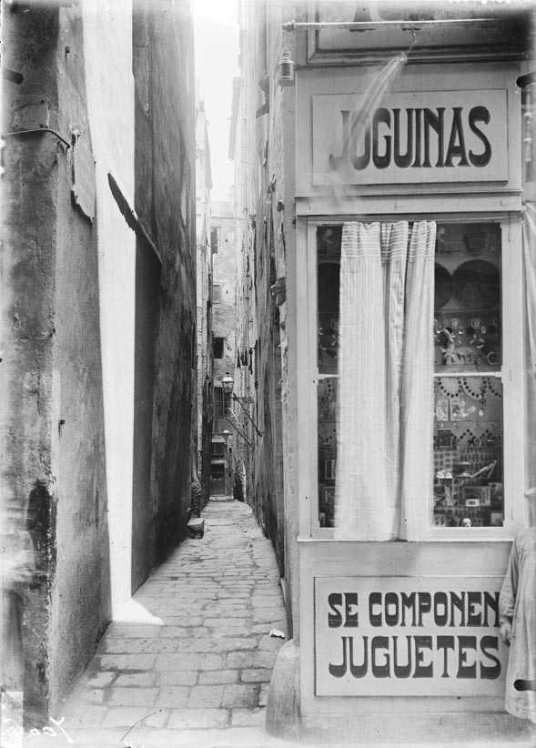 Joguinas. Carrer de les Donzelles, cantonada al carrer Tapineries. 1900-1910 L'entrada per Tapineria era estreta, però l'entrada per la plaça de l'Oli encara ho era més, 1,05 metres: era el carrer més estret de la Barcelona antiga. destruït amb la construcció de la Via Laietana. Es trobava més o menys a la banda mar de l'actual plaça Ramon Berenguer III