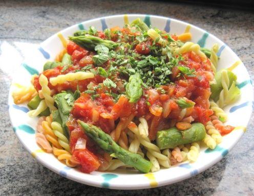 Für die Nudeln mit Spargel und Tomaten den Spargel waschen und holzige Enden abbrechen. Zwiebeln fein schneiden. Gesalzenes Wasser in einem großen