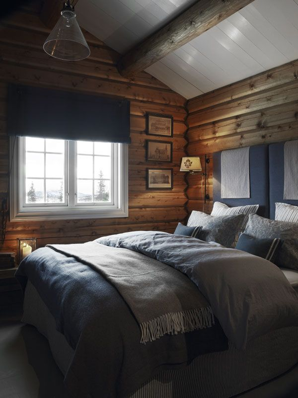 Soverommet er innredet med deilige tekstiler i ulike blå og blågrå nyanser! Det blir en svalt og delikat kontrast til tømmerveggene! Legg ellers merke til det ekstra høye, tekstilkledde hodegjerdet. Behagelig og lunt mot veggen i vinterkulda.