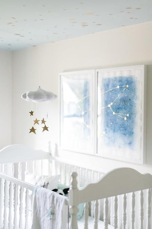 Starry+nursery+with+blue+galaxy+prints+over+a+white+vintage+crib+dressed+in+Aden+