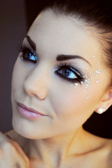 Apply clusters of rhinestones or confetti around your eyes and to your cheeks. Use tweezers to place the pieces, eyelash glue to adhere.